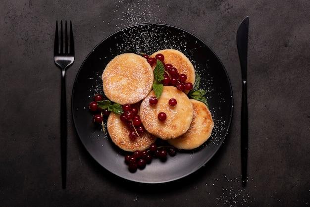 Творожные оладьи с красной смородиной, мятой и сахарной пудрой на черной тарелке