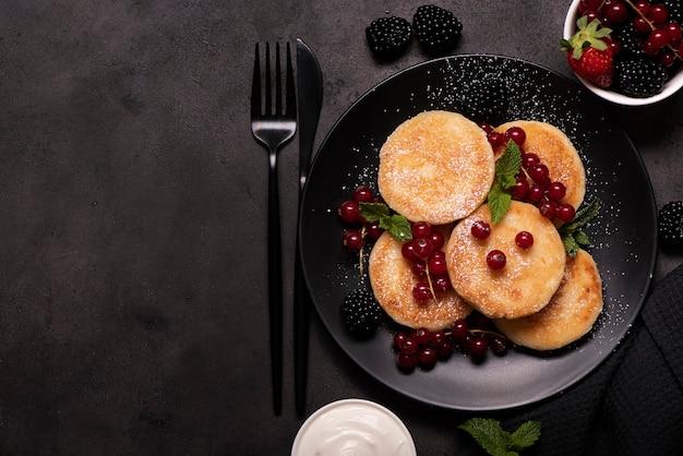黒スグリ、ミント、粉砂糖を黒皿に乗せたカッテージチーズのパンケーキ