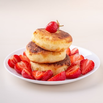 Cottage cheese pancakes with sliced strawberries on white plate isolated angle view