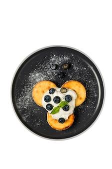 Творожные оладьи со сметаной и черникой, покрытые сахарной пудрой, веточкой мяты, на черной тарелке. изолировано, снято сверху