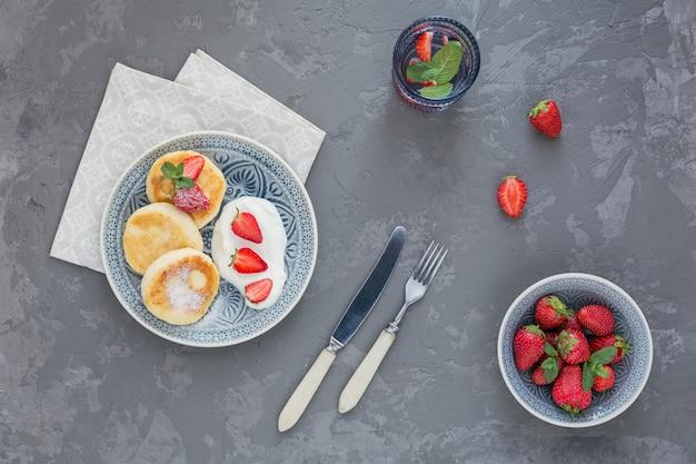 Творожные оладьи со сметаной и клубникой на завтрак или обед на сером. вид сверху