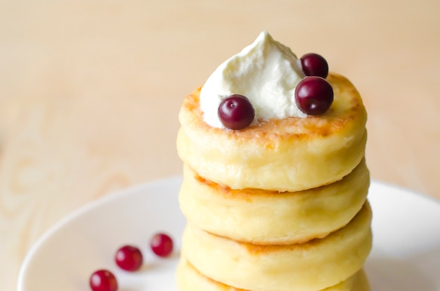 Cottage cheese pancakes with sour cream and berries on rustic background. syrniki.