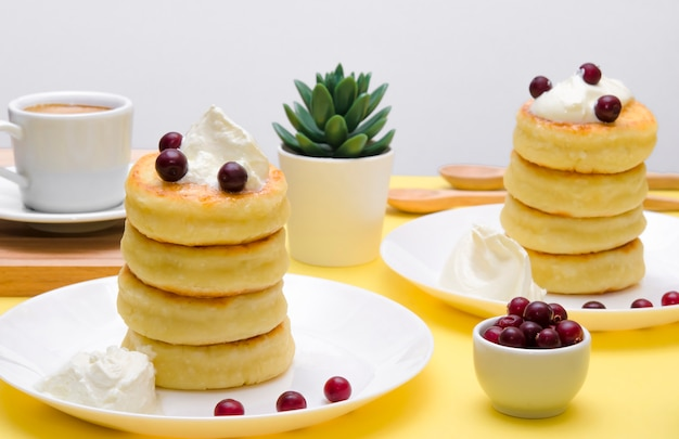 Cottage cheese pancakes with sour cream and berries on yellow background. syrniki.