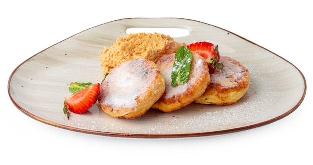 Cottage cheese pancakes with strawberry and sugar powder isolated