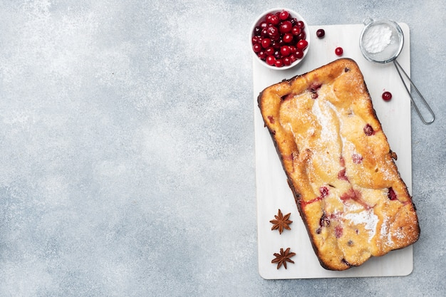 Cottage cheese pie casserole with cranberries and spices sprinkled with powdered sugar on a wooden stand. gray concrete table. copy space