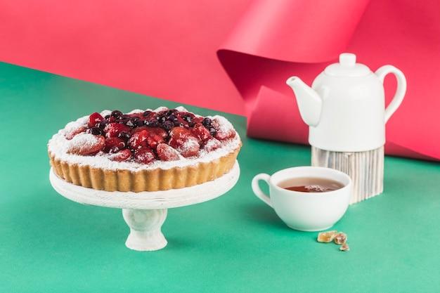 Творожный пирог с ягодами на деревянной подставке на разноцветном фоне с чайником и чашкой чая