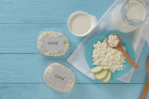 Cottage cheese in plastic packaging and milk top view healthy eating concept