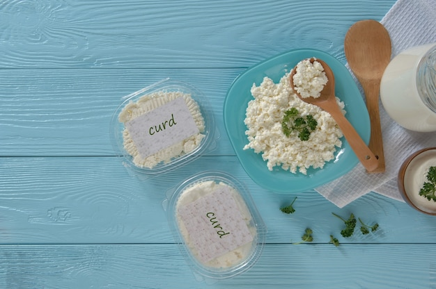 Cottage cheese in plastic packaging and milk on a wooden blue background healthy eating concept