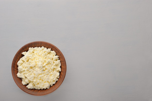 Cottage cheese in the plate on the grey  background.
