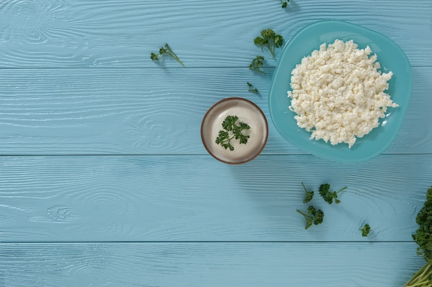 Cottage cheese in a plate and yogurt on a wooden blue background, top view. healthy eating concept