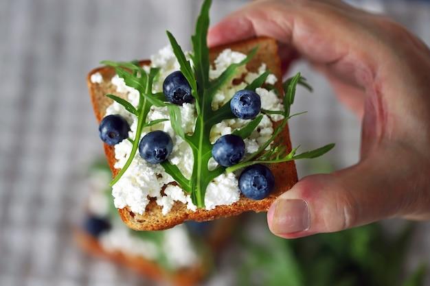 Сэндвич с творогом с творогом и черникой в мужской руке.
