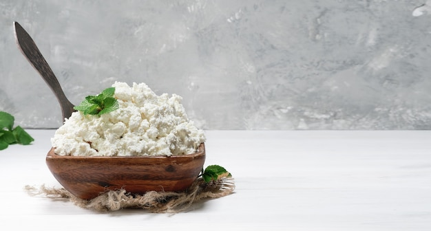 Cottage cheese or soft curd in a traditional wooden bowl with mint leaves on a white wooden background. natural healthy food, wholesome diet food. close-up, selective focus with copy space.