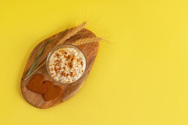 Творог посыпанный крошкой от печенья, печенье с корицей в форме сердца, колосья пшеницы на деревянной доске на желтой поверхности