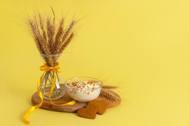 Творог посыпанный крошкой от печенья, печенье с корицей в форме сердца, стеклянная ваза, колосья пшеницы на деревянной доске на желтой поверхности