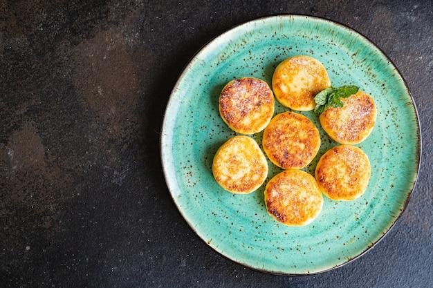 カッテージチーズ甘いパンケーキチーズケーキ豆腐朝食デザートシルニキ健康的な食事、上面図 Premium写真