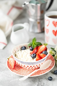 Cottage cheese with berries, jam, fresh strawberries and a cup of coffee with cream for breakfast.