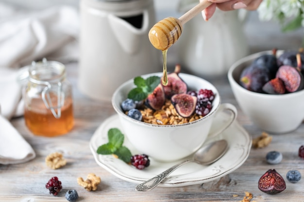 Cottage cheese with figs, berries, honey. cup of coffee and coffee pot. breakfast. wooden table.