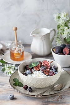 Cottage cheese with figs, berries, honey and cup of coffee with coffee pot
