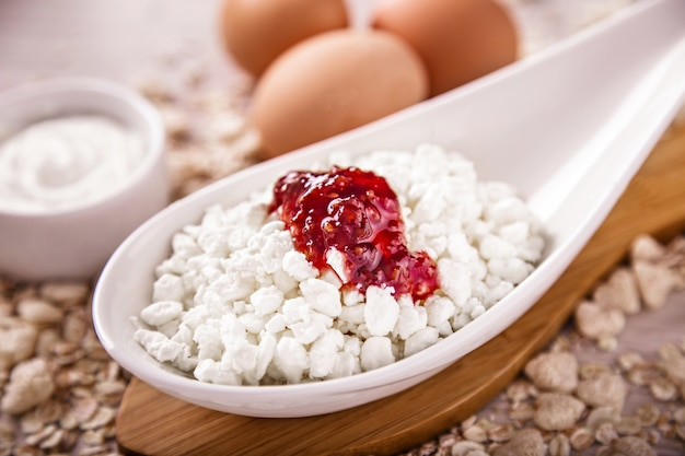 Cottage cheese with jam and eggs on the surface of scattered muesli