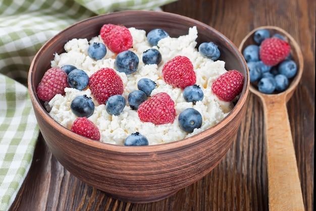 나무 딸기와 갈색 점토 그릇에 블루 베리와 갈색 나무 배경에 나무 숟가락 코티지 치즈