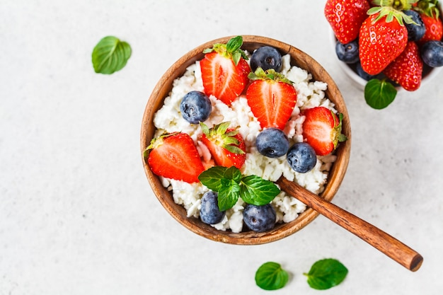 Cottage cheese with strawberries and blueberries in wooden bowl