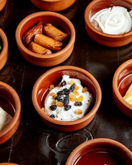 Cottage cheese with sultanas and sausages in earthenware