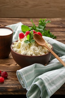 Cottage cheese with wooden spoon and milk in clay cup