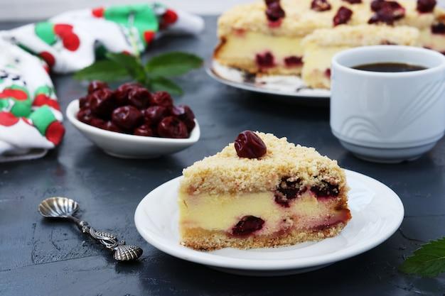 Творожный пирог с вишней, расположенный на тарелке на темном фоне