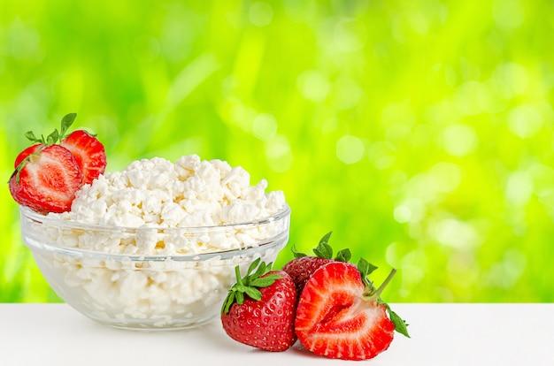 흐리게 추상 여름 배경에 딸기와 코 티 지 또는 두 부 치즈. 공간 복사
