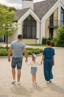 In cottage town. stylish family feeling good while enjoying evening walk in the cottage town