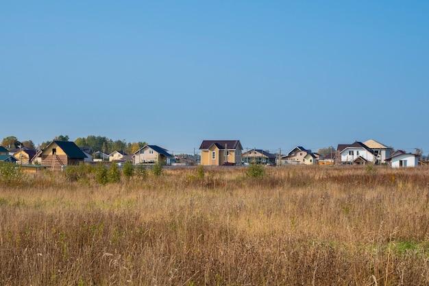 コテージビレッジ。乾燥した黄色のフィールドにあるモダンなコテージ村の秋の景色。ロシア。