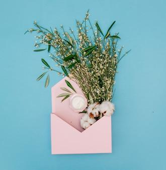 Хлопок и сливки с травами в розовом конверте на синем фоне. вид сверху
