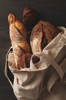 Cotton bag with bakery products on black background
