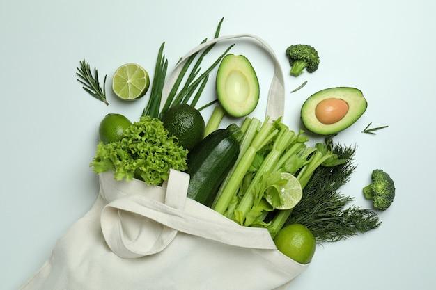 Хлопковый мешок с зелеными овощами на белом