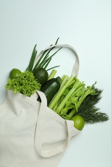 Cotton bag with green vegetables on white