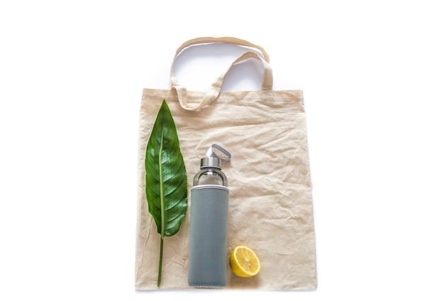 Хлопковый мешок с бутылкой с водой плоды сырых лимонов зеленые листья на плоской белой стене. безотходный многоразовый экологически чистый материал без пластика