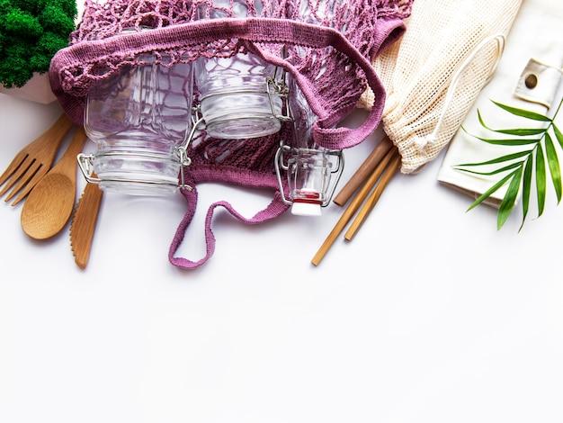 Хлопковые мешки, сетчатый мешок с многоразовыми стеклянными банками, бамбуковые и деревянные столовые приборы на белой поверхности. концепция нулевых отходов. экологичный. плоская планировка