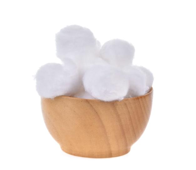 Ватные шарики в деревянной миске на белом фоне
