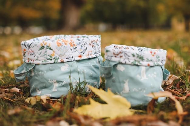 秋の背景の紅葉の間の草の上の綿のバスケットまたはバッグ Premium写真