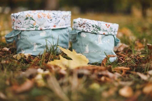 秋の背景の紅葉の間の草の上の綿のバスケットまたはバッグ
