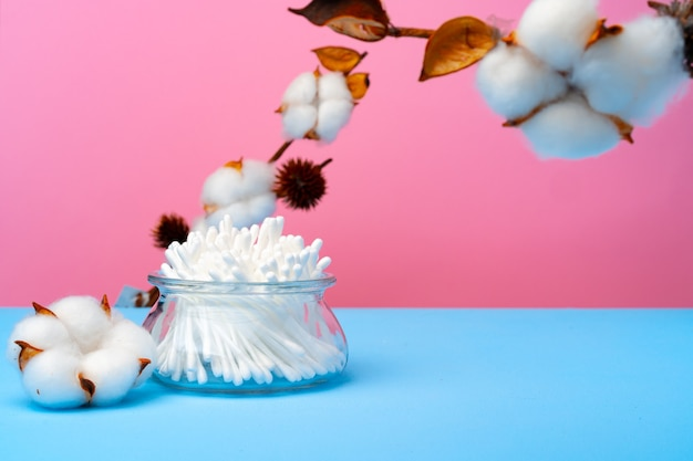 Cotton buds for cleaning ears on pink and blue background