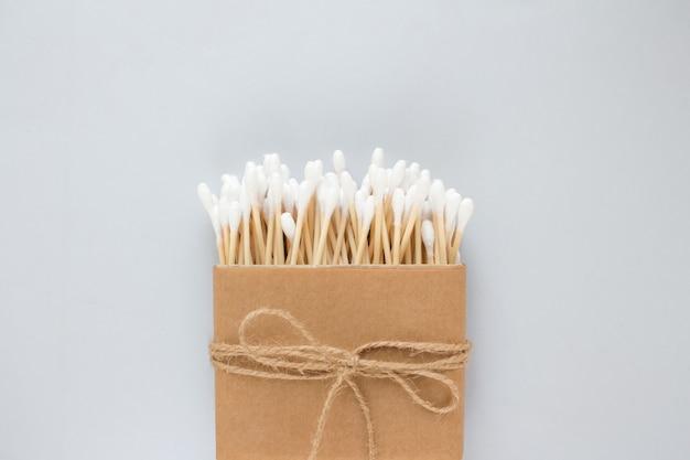 灰色のテーブルの紙箱の綿棒