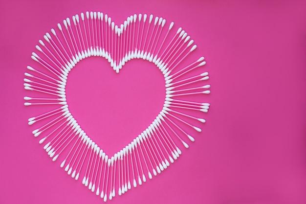ピンクの背景にハートの形に配置された綿棒。
