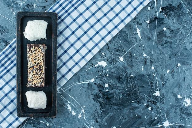 Ватные конфеты и шоколадные вафли на деревянной тарелке на кухонном полотенце, на синем столе.