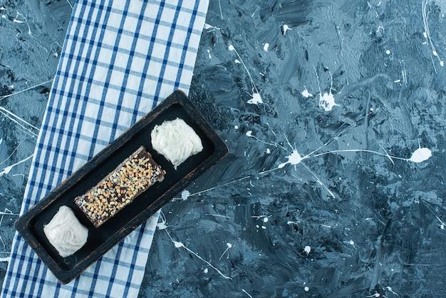 青いテーブルの上に、ティータオルの上の木のプレートに綿菓子とチョコレートワッフル。