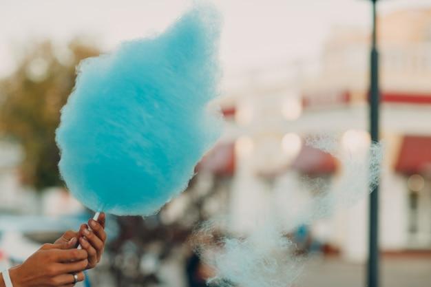 屋外で青いキャンディフロスを作る綿菓子フロスマシン。
