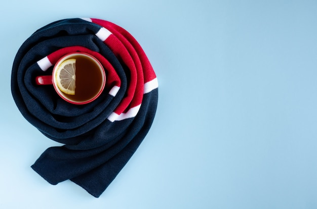 Cotton colored scarf with tea cup and lemon slice composition on blue background.