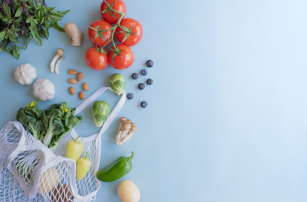 Хлопок эко сетчатая сумка со свежими овощами и фруктами на плоской заложить синий фон. без пластика для покупки продуктов и доставки. безотходный образ жизни. здоровая пища и веганская диета.