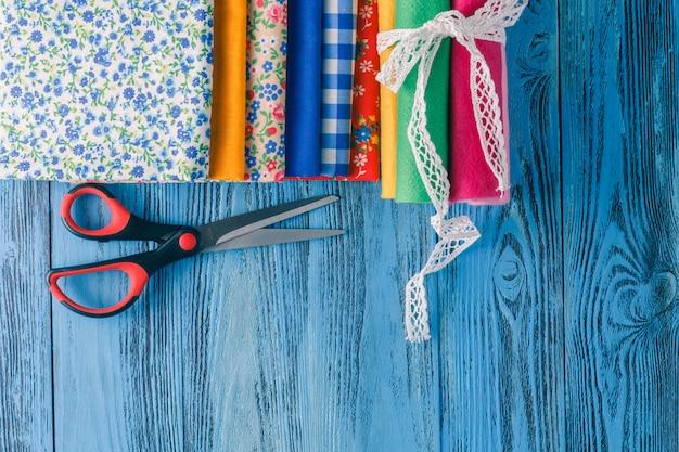 Хлопчатобумажные ткани для шитья, кружева и аксессуары для рукоделия на деревянных фоне.