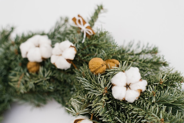 Cotton flower and walnuts in christmas wreath, close-up of wreath